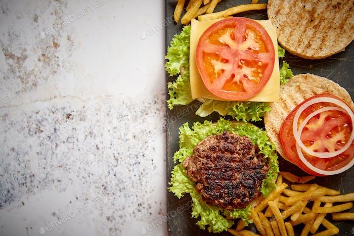 Zwei leckere gegrillte hausgemachte Burger mit Rindfleisch, Tomaten, Zwiebeln und Salat