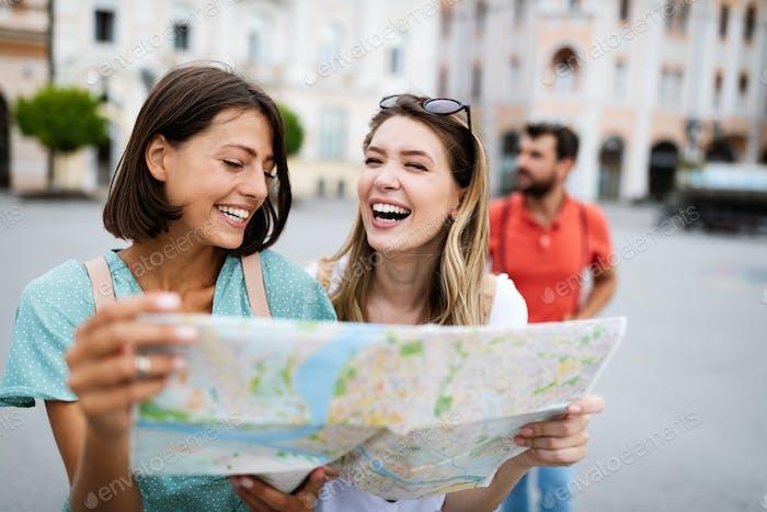Vacaciones, viajes, amigos y concepto turístico. Chicas hermosas mirando en el mapa turístico de la ciudad