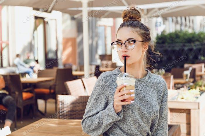 Mujer joven en la calle café bebe cóctel y mira hacia otro lado