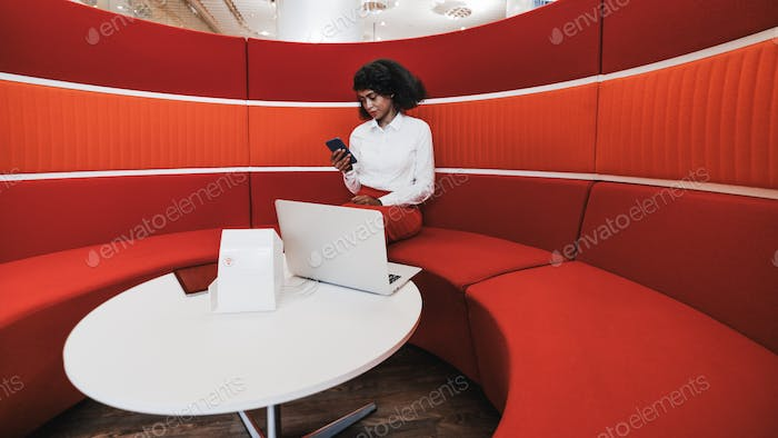 A businesswoman on a red bent sofa