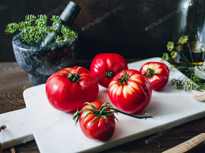Ripe tomatoes on a white marble kitchen board. Cooking concept.