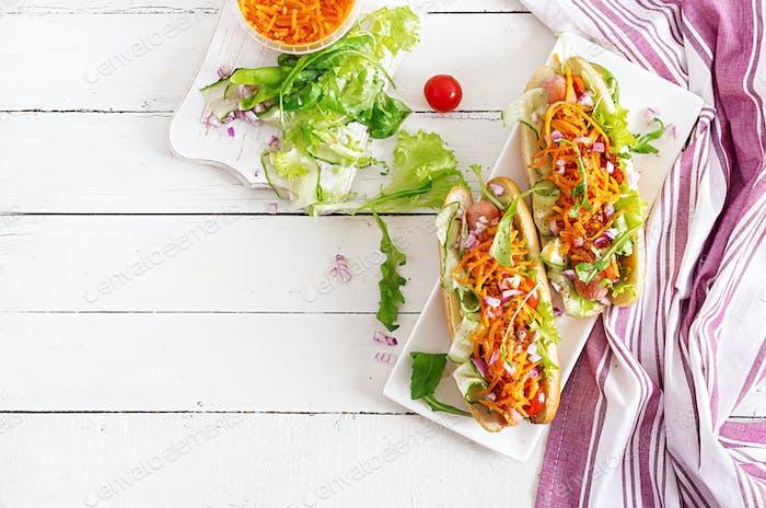 Hot Dog mit Gurke, Karotte, Tomaten und Salat auf hölzernem Hintergrund. Fast-Food-Menü. Ansicht von oben