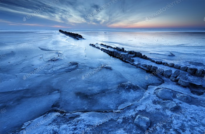 alte hölzerne Wellenbrecher an gefrorener Küste