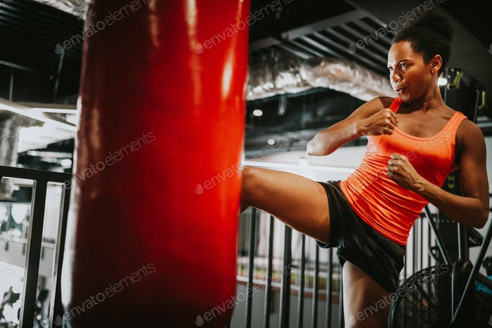 Beautiful fit woman in sportswear boxing kicking bag in the gym
