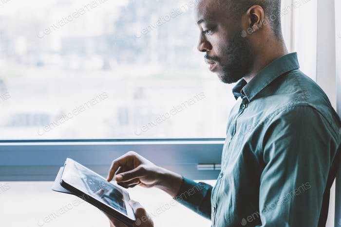 Half length of young handsome afro businessman near a window hol
