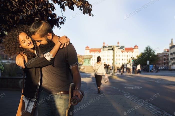Lächelnde Freunde umarmen auf Bürgersteig