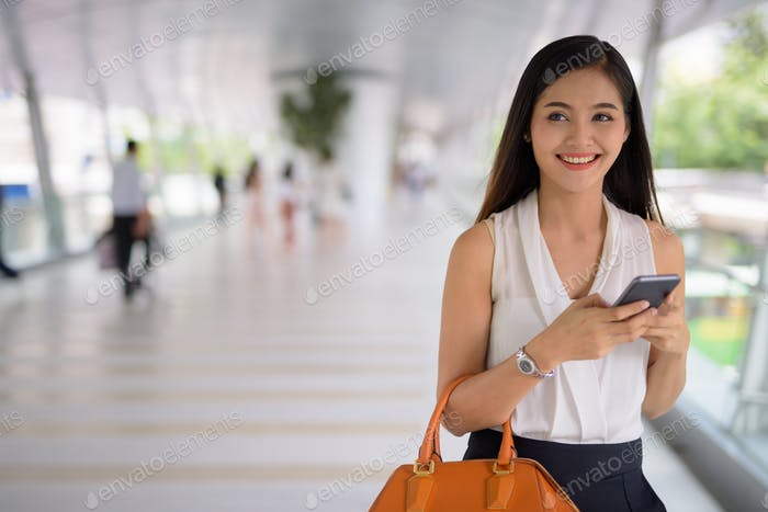 Young beautiful Asian businesswoman hanging out at the footbridg