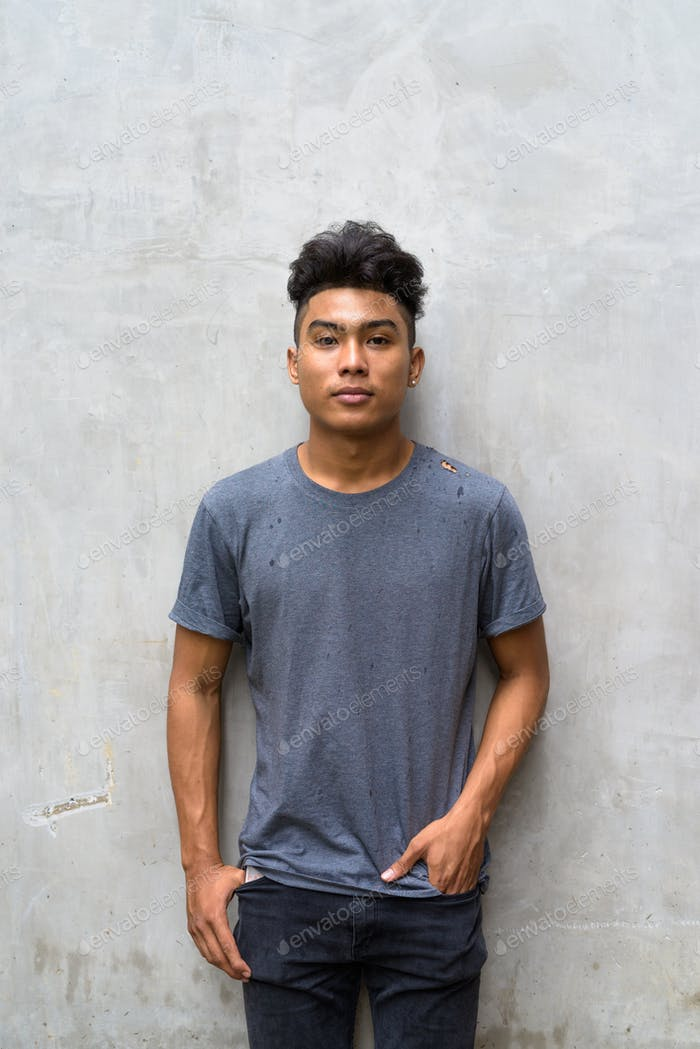Young Asian man with curly hair against concrete wall outdoors