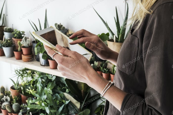 Close up of female owner of plant shop holding digital tablet, a selection of plants on wooden