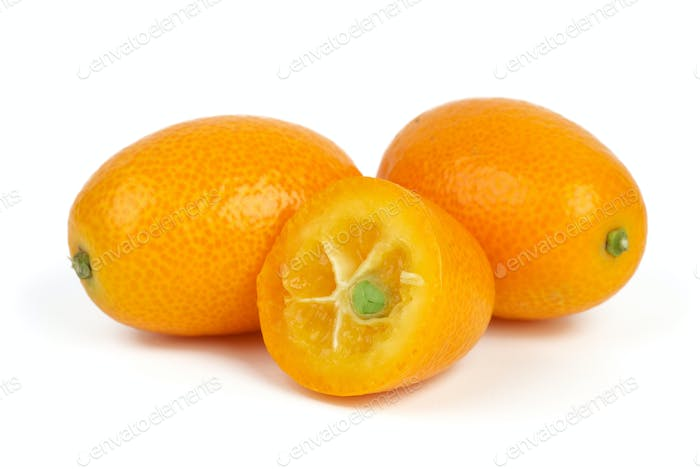 Two whole and sliced kumquat fruits