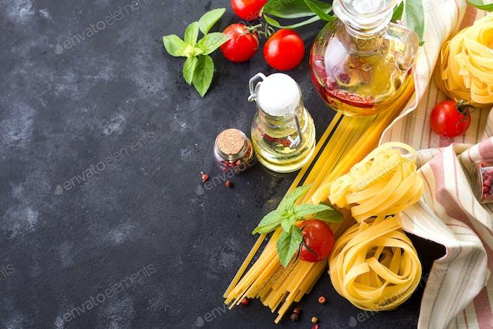 Food ingredients for Italian spaghetti on black stone slate background