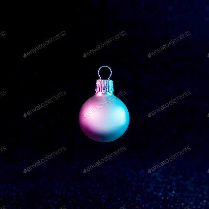Christmas bauble decoration in vivid neon colors. Christmas dark background concept.