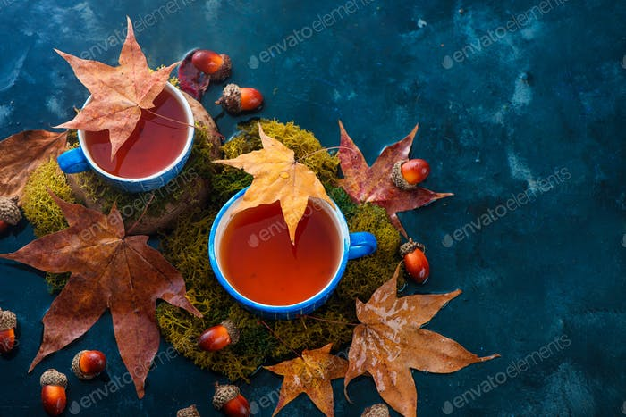 Autumn drink photography with hot tea in blue ceramic cups and fallen maple leaves on a wet dark