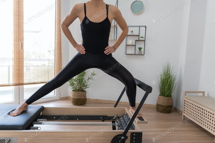 Young woman exercising on pilates reformer bed