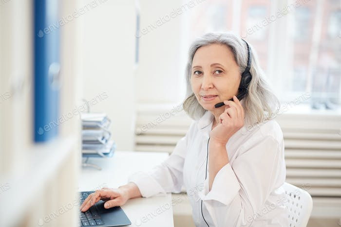 Senior Businesswoman Wearing Headset at Workplace