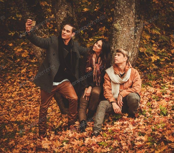 Friends making selfie in an autumn park