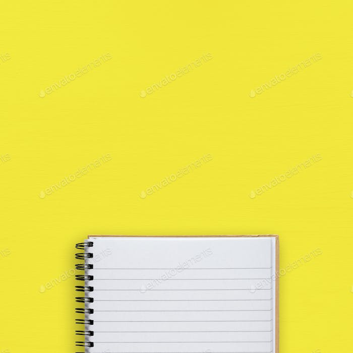 Notepad on yellow background top view