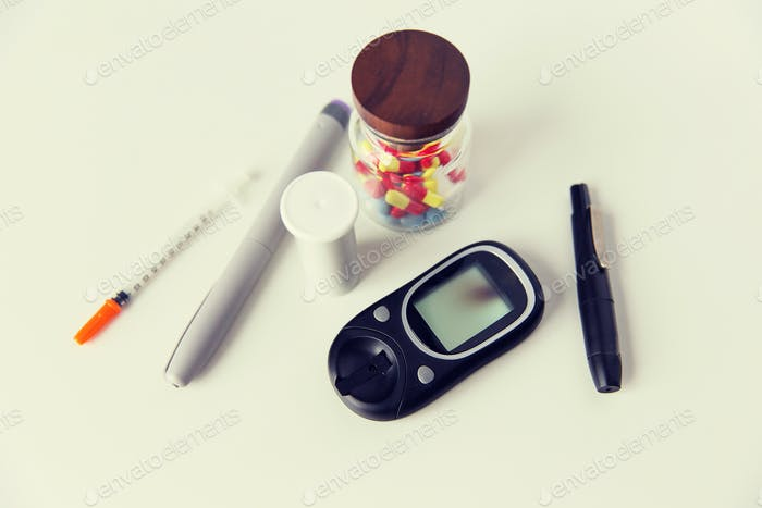 close up of glucometer, insulin pen and drug pills