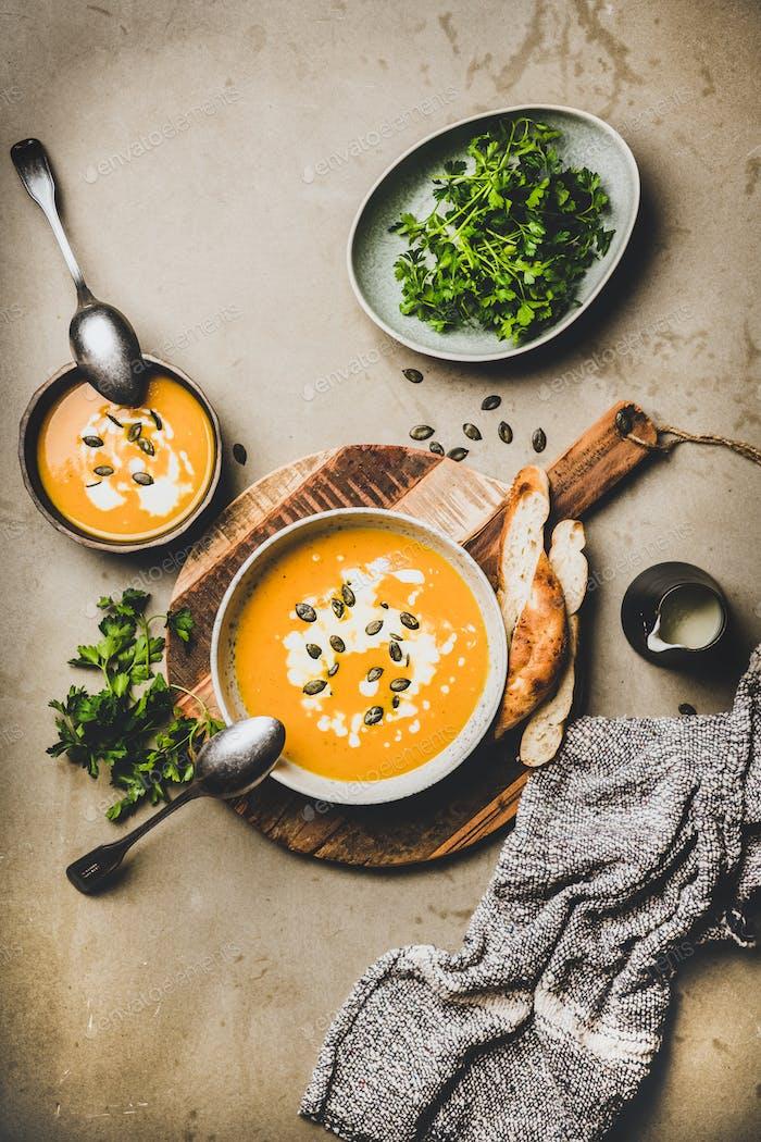 Flat-Lay Kürbis-Sahnesuppe mit Samen, Petersilie und Sahne