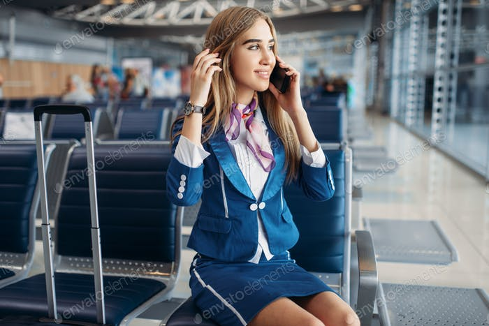 Stewardess talking by mobile phone in airport
