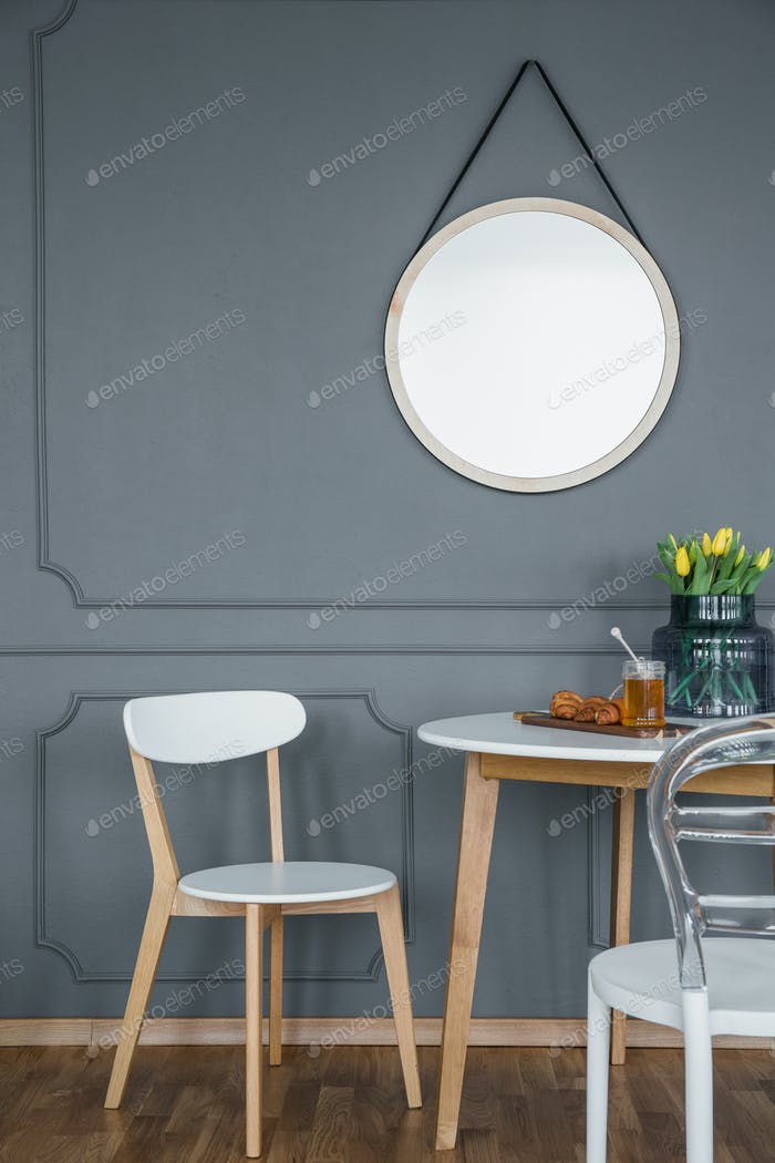 Round mirror above dining set