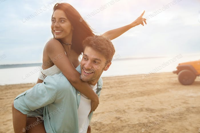 Handsome man giving a piggyback ride to his smiling girlfriend