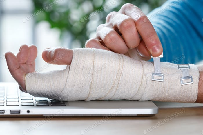 man arms wrapping his painful wrist with orthopedic bandage