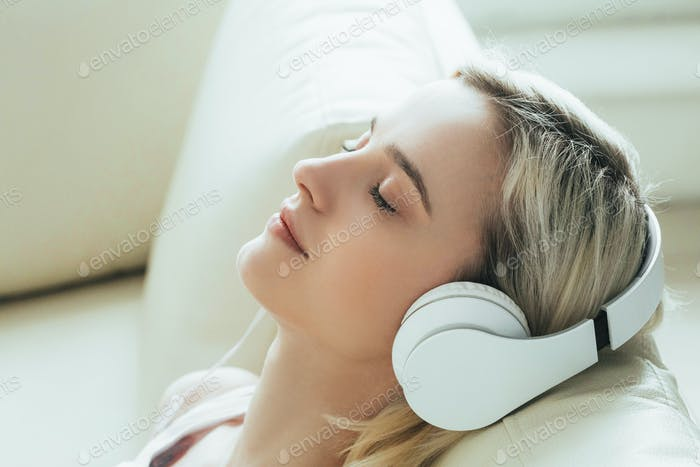 Woman in headphones at home listening to music, relax alone close up portrait.