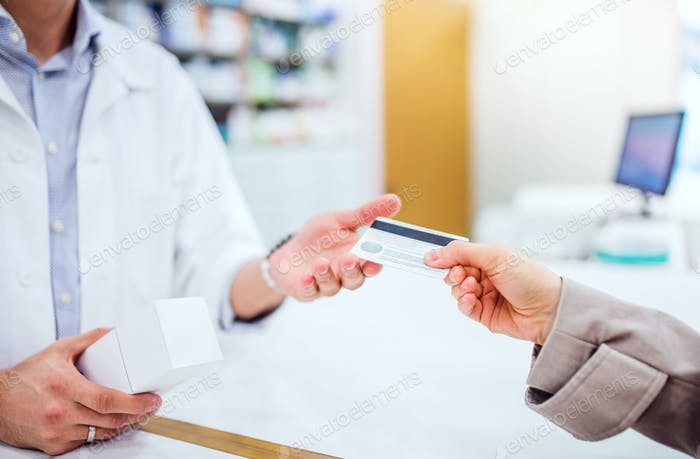 Unrecognizable customer giving a credit card to a male pharmacist.