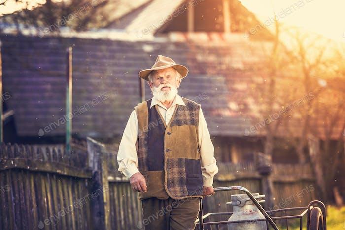 Senior man with milk kettle