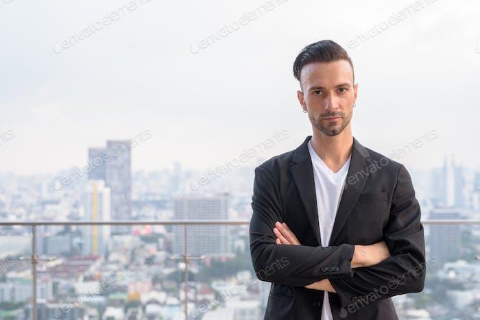 Porträt eines Geschäftsmannes, der auf dem Dach eines Wolkenkratzers steht