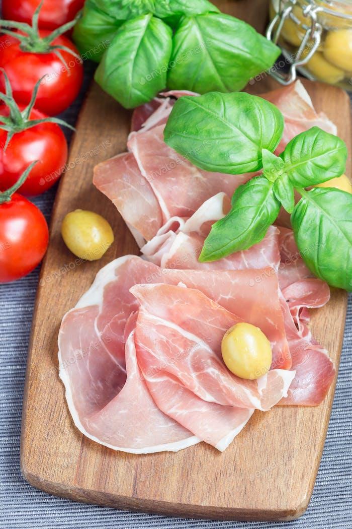 Schinken auf Holzbrett mit grünen Oliven, Tomaten und Bas