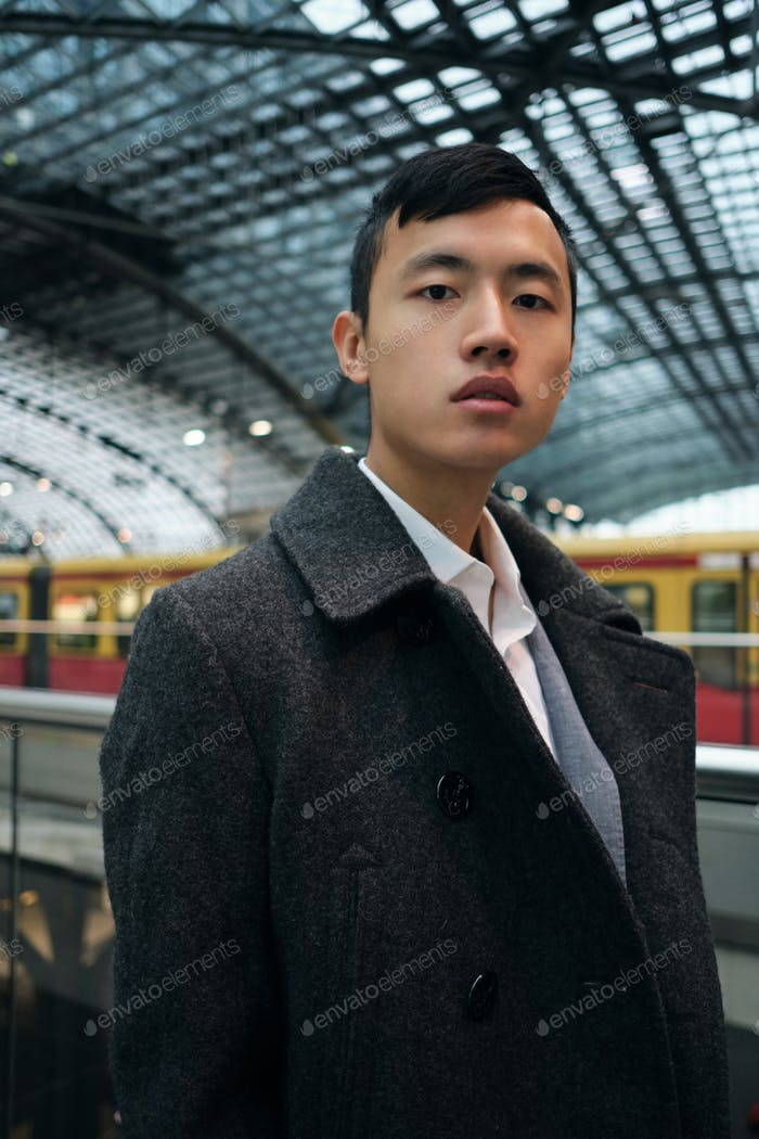 Young stylish Asian businessman confidetly looking in camera at metro station