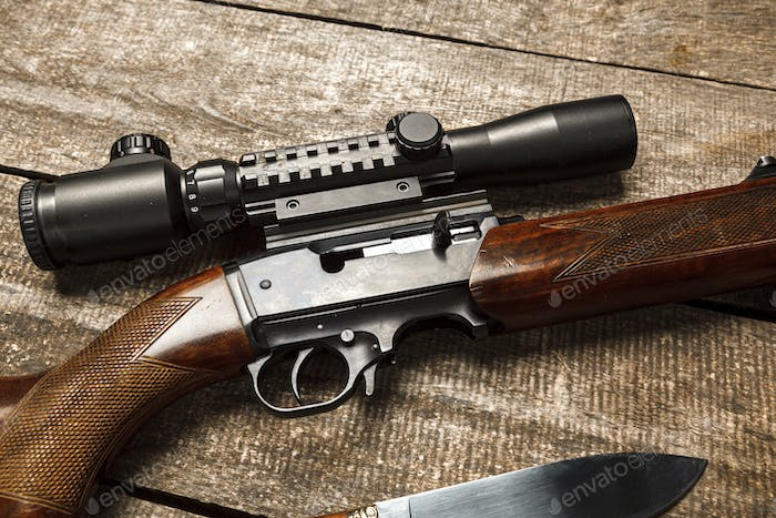 The optical sight and shotgun on wooden backgorund