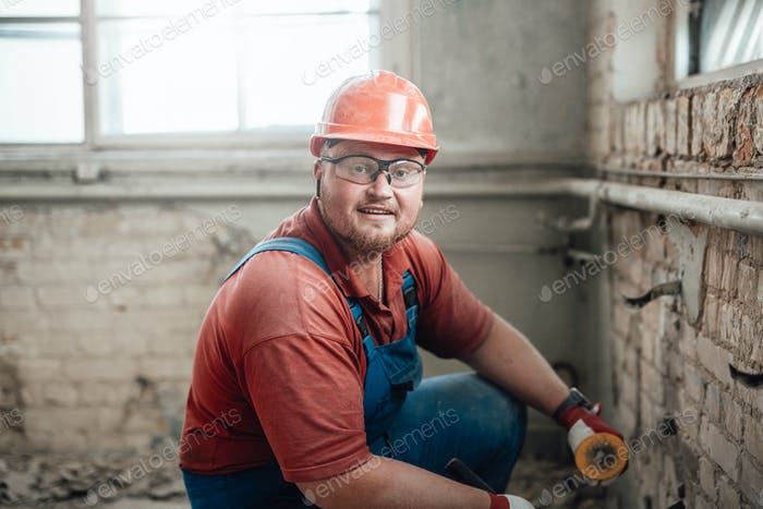 Builder in a protective helmet on a construction site working on a brick wall