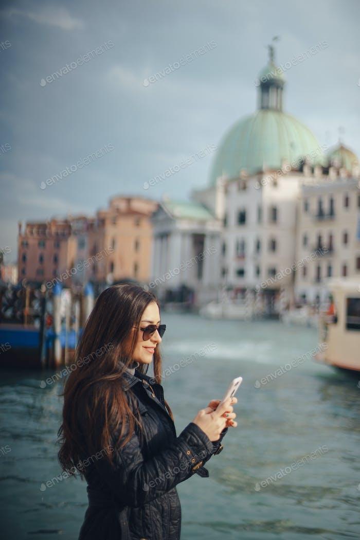 Mädchen im Gespräch am Telefon und fotografieren in Venedig