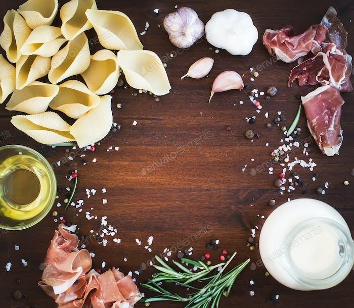 Carbonara pasta ingredients: conchiglioni, bacon, a jug of cream