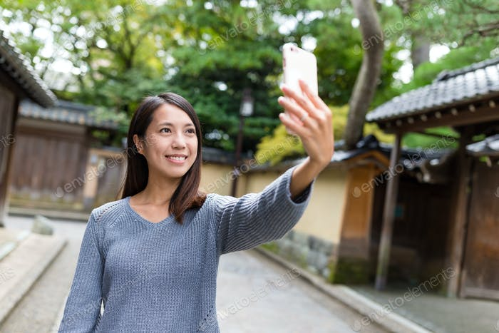 Woman taking selfie by smart phone