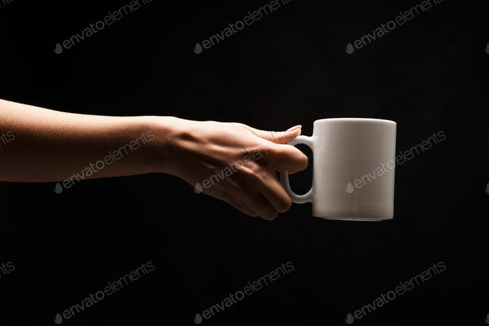 Woman holding white coffee cup on black background