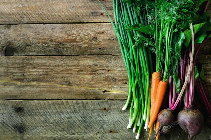 Fresh vegetables - carrots, beetroots, green onion on wooden background. Harvest. Concept of diet