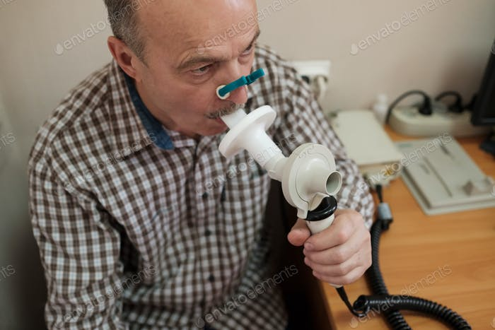 Senior hispanic man man testing breathing function by spirometry