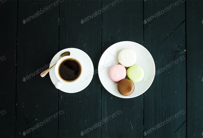Macaron cookies, cup of espresso over black wooden backdrop