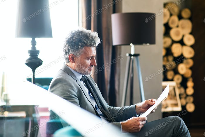 Mature businessman reading in a hotel lounge.