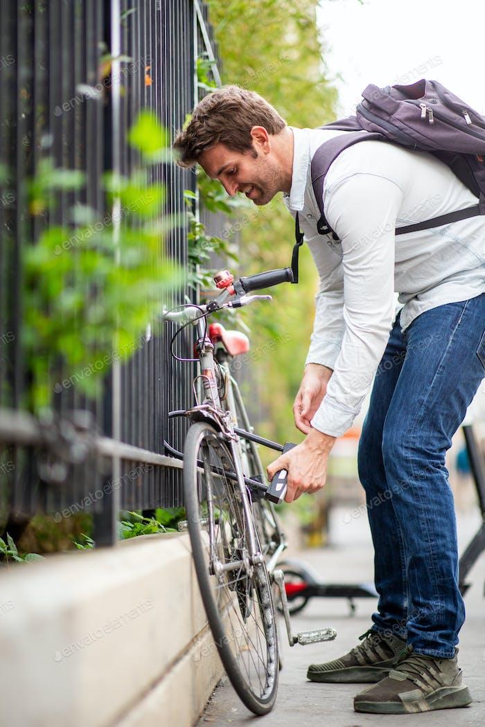 man with bag unlocking bicycle on city street