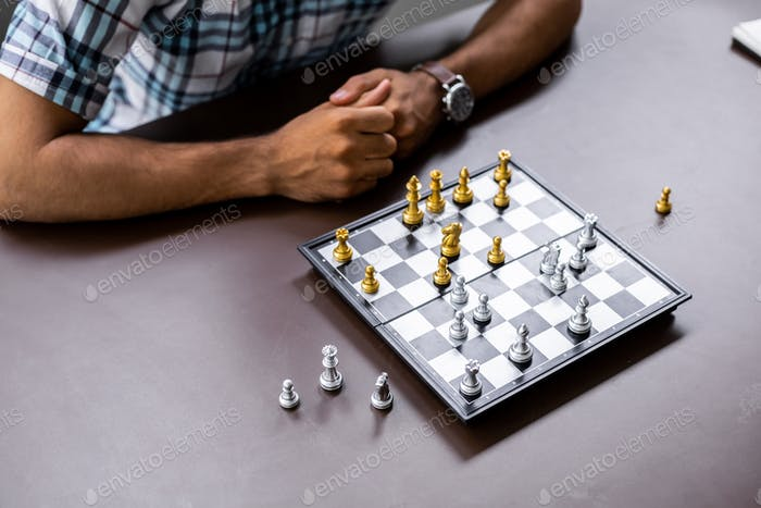 Man developing chess strategy, playing board game.