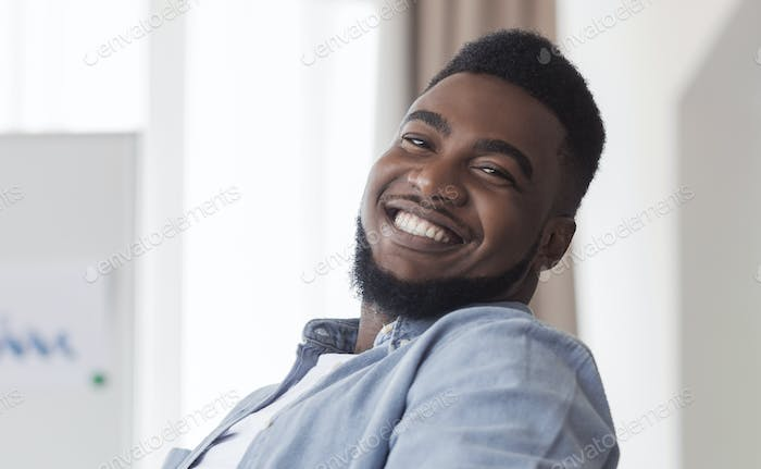 Closeup portrait of cheerful african american guy indoors