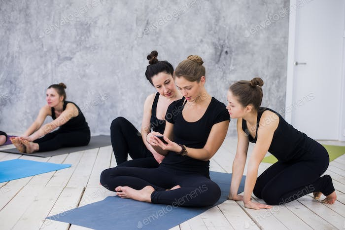 Cute girl sitting and socializing with the group after their yoga class