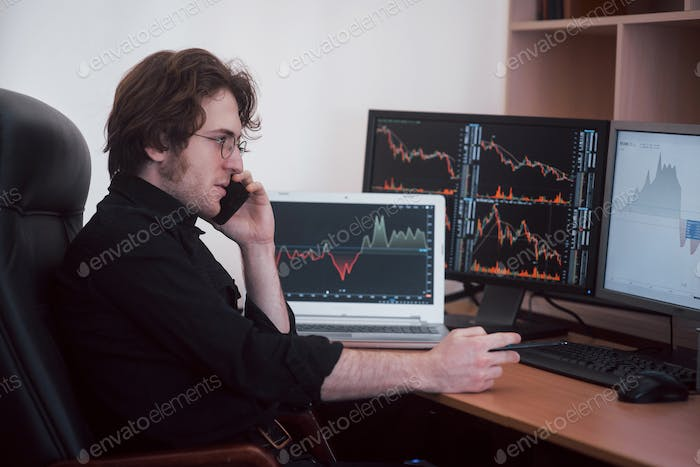 Over the shoulder view of and stock broker trading online while accepting orders by phone