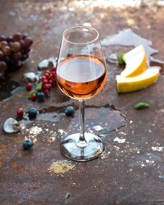 Copa de vino rosa con bayas, melón, uvas y Hielo sobre Fondo de Metal oxidado grunge
