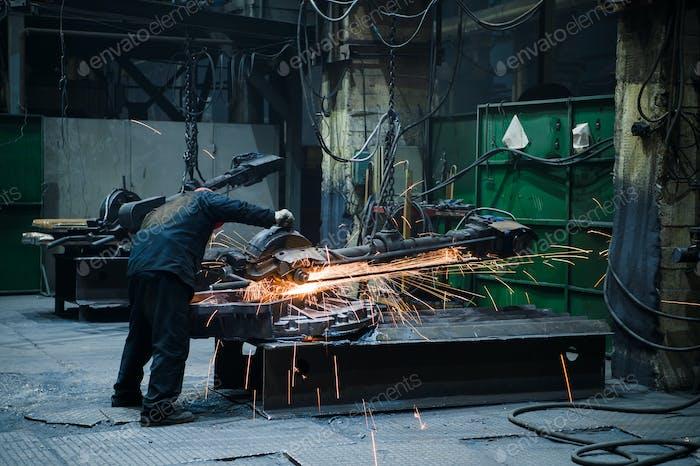 Industriearbeiter mit Arbeitswerkzeug. Große Kettensäge in den Händen in der Stahlfabrik